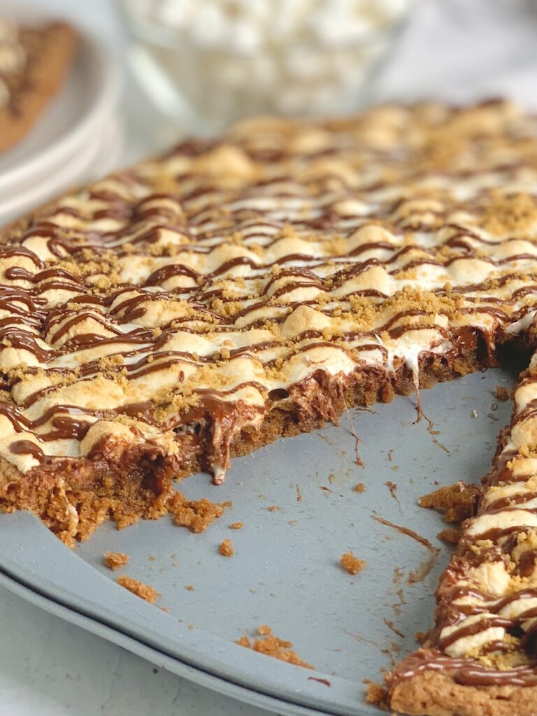 A pizza pan layered with a graham cracker crust, melted chocolate, golden brown mini marshmallows, then drizzled with chocolate and topped with graham cracker crumbs. A large slice is removed from the pizza and placed on a plate nearby.