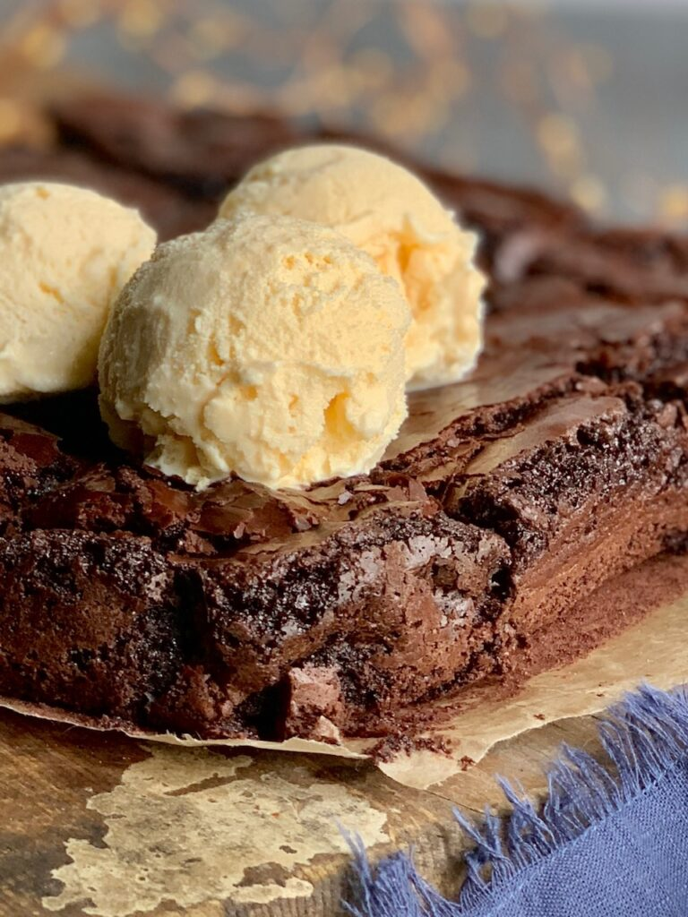 An 8x8-inch square baked brownie cut into 12 slices on a cutting board and 3 dollops of ice cream on top.