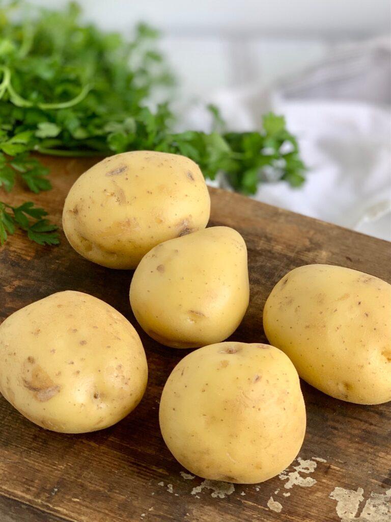 5 Yukon Golden Potatoes on a cutting board.