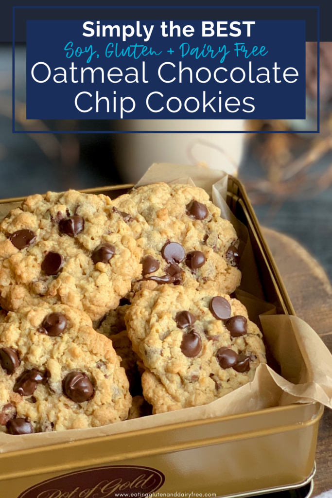 A gold colored cookie tin packed full of golden brown cookies loaded with chocolate chips next to a cup of milk.