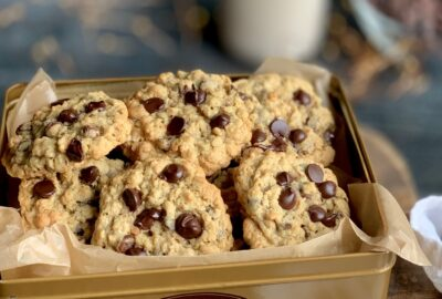 A tan cookie tin loaded with golden round cookies with oatmeal and chocolate chips.