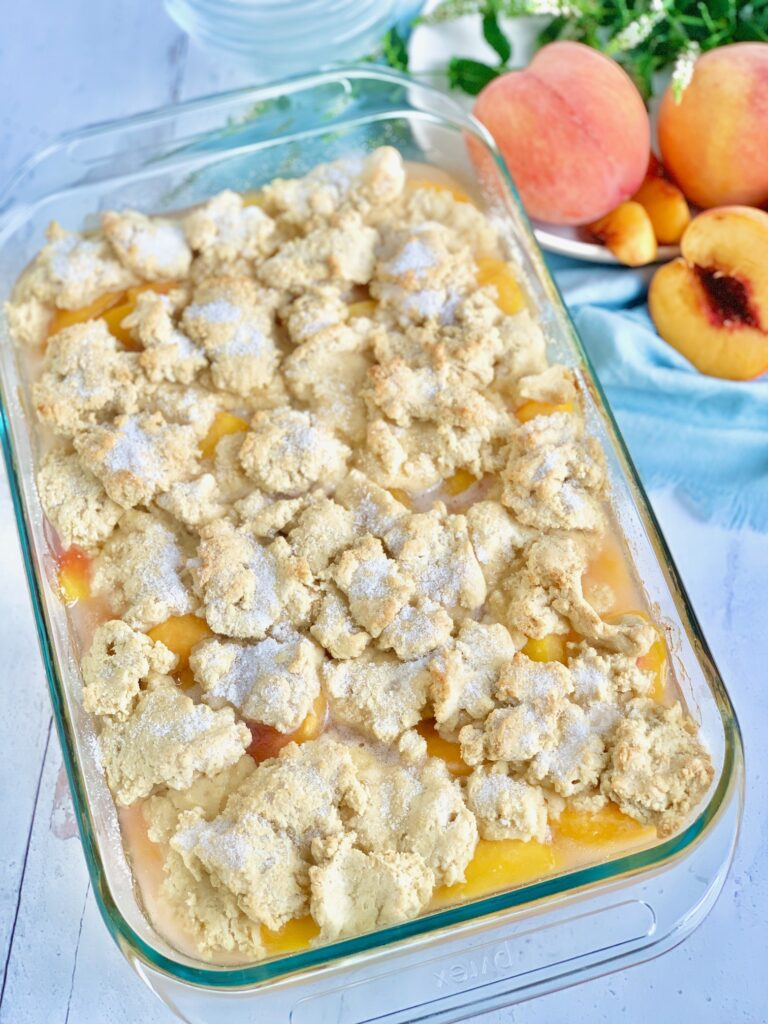 A 9x13-inch baking dish filled with a thick sweet peach mixture and topped with a biscuit-like golden brown dough.