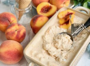 A bread loaf pan filled with peach flavored ice cream. An ice cream scoop is scooping some out. Nearby are several fresh peaches and an ice cream cone.