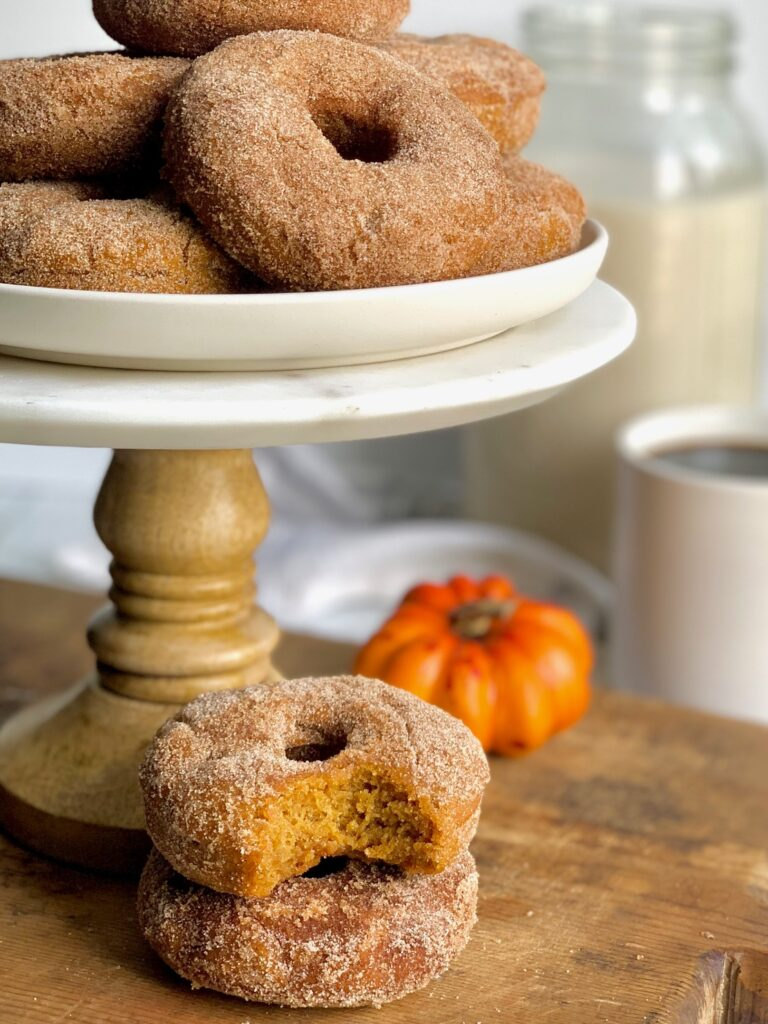 Several donuts stacked on top of each other on a white plate on top of marble cake stand.
