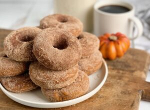 A white plate loaded with several pumpkin donuts covered with cinnamon sugar.