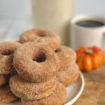 Several donuts stacked on top of each other on a white plate next to a cup of coffee and a decorative pumpkin.