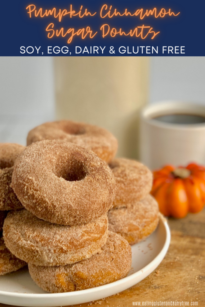 Several donuts stacked on top of each other with a cinnamon sugar coating on a white plate next to a cup of coffee and a decorative pumpkin.