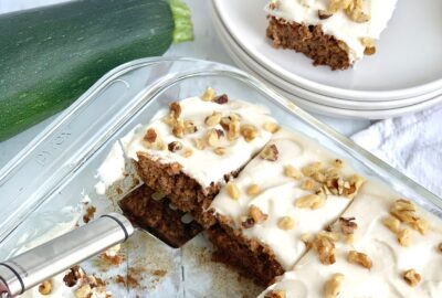 A glass baking pan filled with a golden colored cake and cream cheese frosting on top with scattered chopped walnuts next to a whole zucchini and white serving plates.