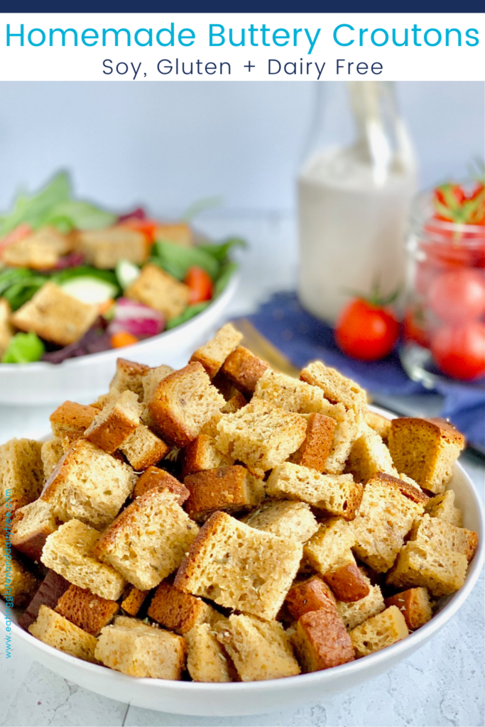 A large bowl with cubed, crispy, croutons in it with a salad in the background and mini grape tomatoes.