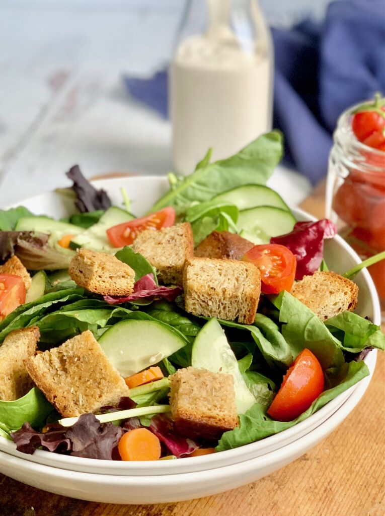 A large bowl filled with crisp greens, sliced cucumbers and grape tomatoes, and topped with buttery croutons.
