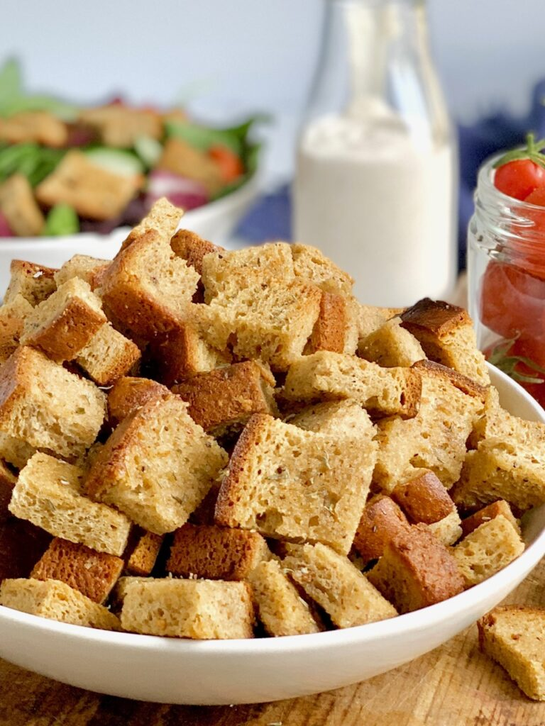 A large bowl with cubed, crispy, croutons in it next to a jar of grape tomatoes.
