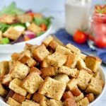 A large bowl with cubed, crispy, croutons in it with a salad in the background.