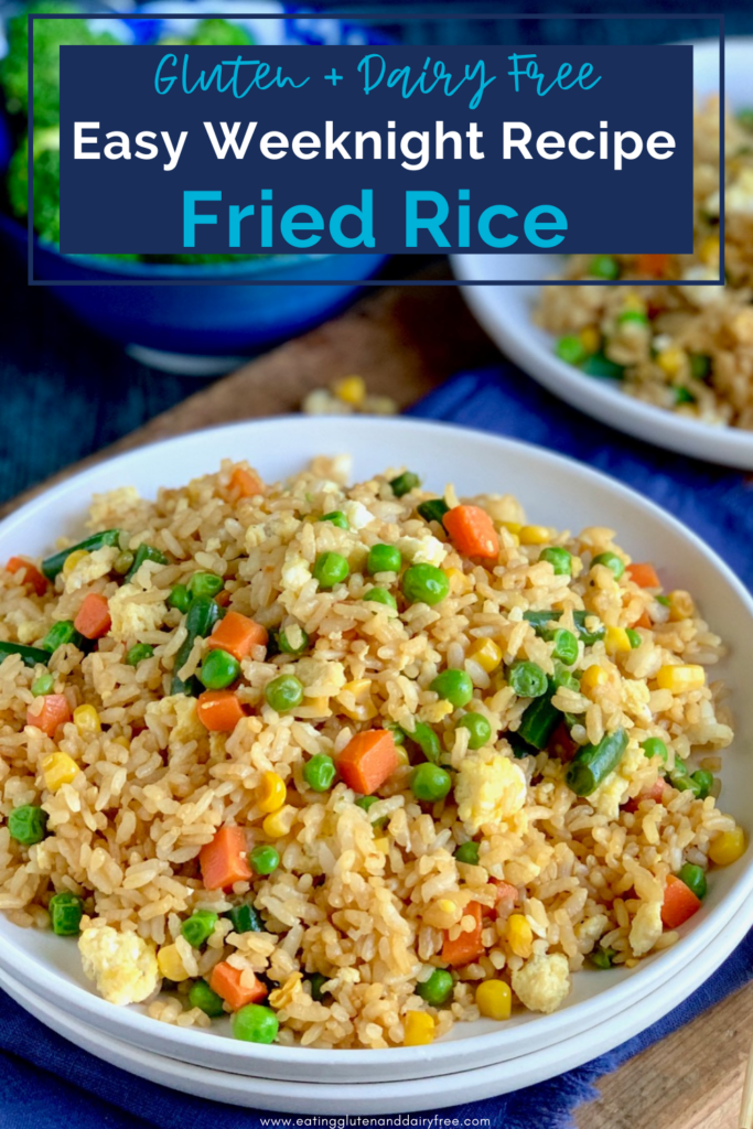 A large white plate piled with golden brown rice with small cubed carrots, peas, corn, and green beans.