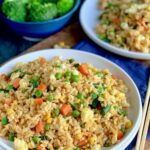 A large white plate piled with golden brown rice with small cubed carrots, peas, corn, and green beans next to chopsticks and a bowl of broccoli.