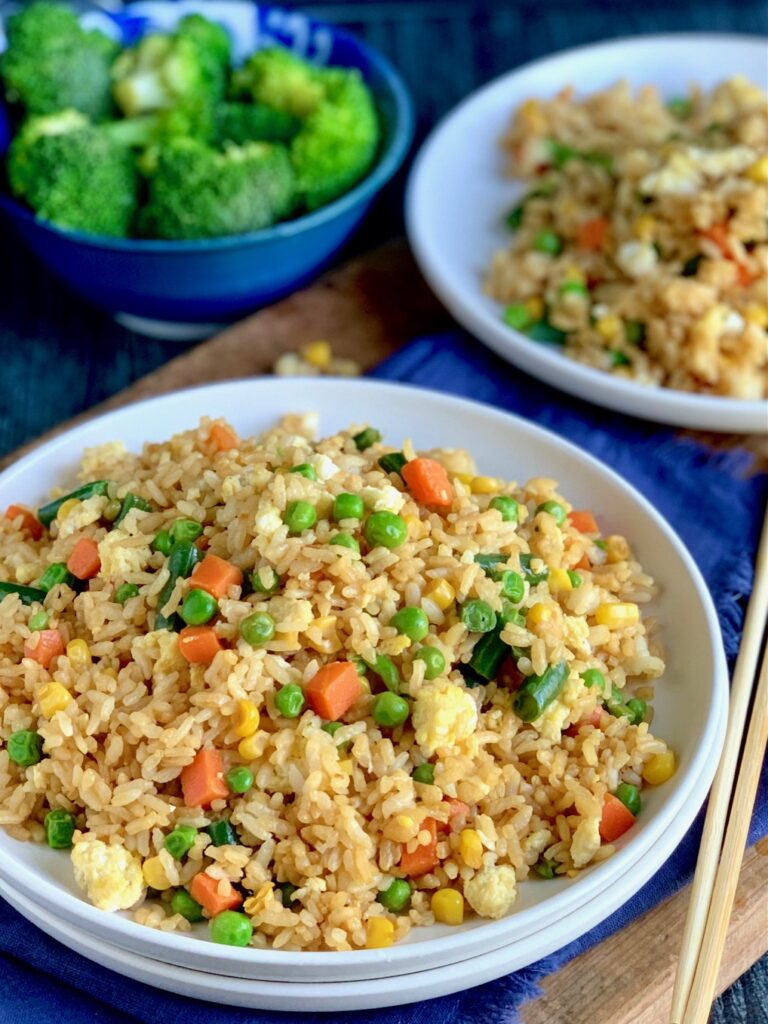A large white plate piled with golden brown rice with small cubed carrots, peas, corn, and green beans next to chopsticks and a bowl of broccoli