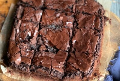An 8x8-inch square pan of baked brownies on a cutting board.