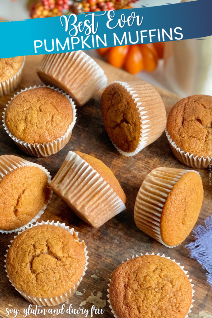 Pumpkin colored muffins in white muffins liners scattered across a dark serving platter.