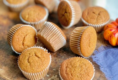 A dark serving platter full of pumpkin colored muffins scattered across it.