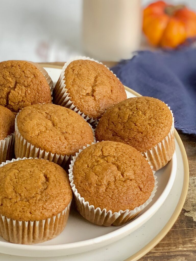 Pumpkin colored muffins in white muffins liners on a white plate across a dark serving platter.