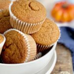A white bowl full of pumpkin colored muffins in white muffins liners.