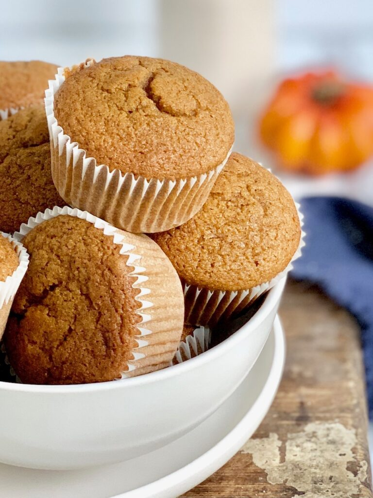 Pumpkin colored muffins in white muffins in a large white bowl.