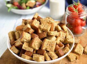 A bowl full of crispy, buttery croutons .